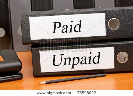 Paid and Unpaid - two binders on desk in the office