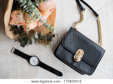 Feminine tabletop, flowers, elegant handbag and wrist watch on white textured background.
