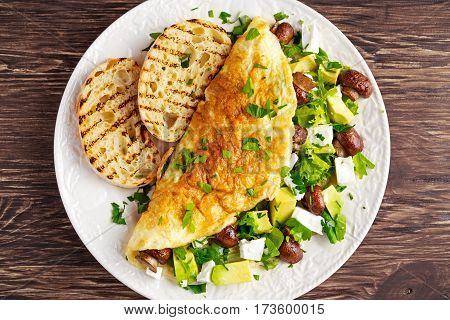 Mushroom, Feta Cheese egg Omelette witch Avocado, vegetables, lettuce, herbs and grilled bread