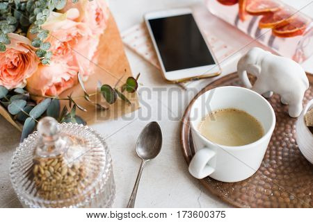 Feminine tabletop, home office with flowers, coffee and smartphone on white textured background, blogger's workplace