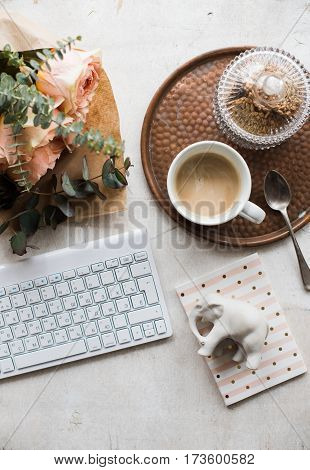 Feminine tabletop, home office with flowers, coffee and keyboard on white textured background, blogger's workplace