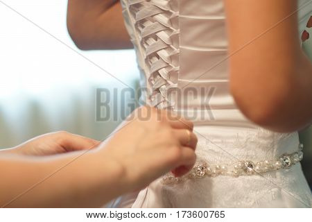 A mother prepares her daughter to the wedding, corset lacing wedding dress, lace