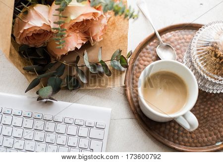 Feminine tabletop, home office with flowers, coffee and keyboard on white textured background, blogger's workplace.