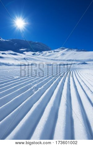 Ski track in snow as abstract background bright winter sun on clear blue sky