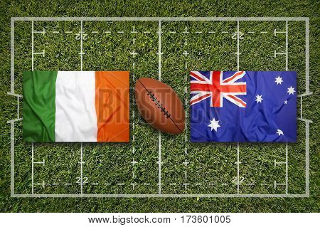 Ireland vs. Australia flags on green rugby field, 3 D illustration