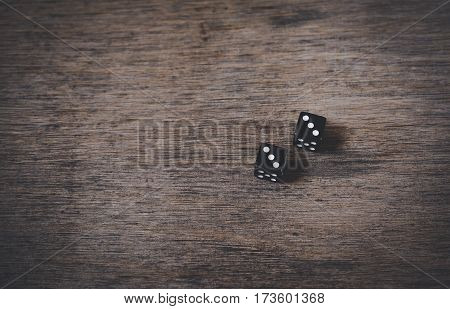 pair of old black dices on rustic wood table