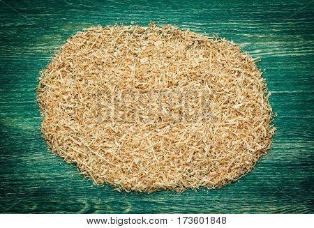 Thin, soft, twisted wood shavings on the green wooden background. Top view