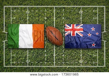 Ireland vs. New Zealand flags on green rugby field, 3 D illustration