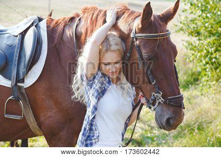 Beautiful blonde girl hugging her brown horse. Summer photo in warm tones