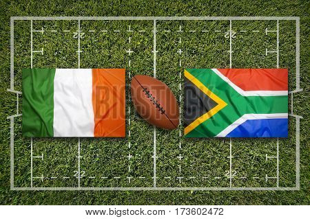 Ireland vs. South Africa flags on green rugby field, 3 D illustration