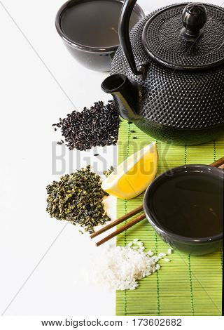 Asian green tea set on bamboo mat with dried green tea lemon black and white rice with copy space. Asian tea concept.
