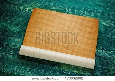 Rolls of empty blueprint on green wooden board. Top view.