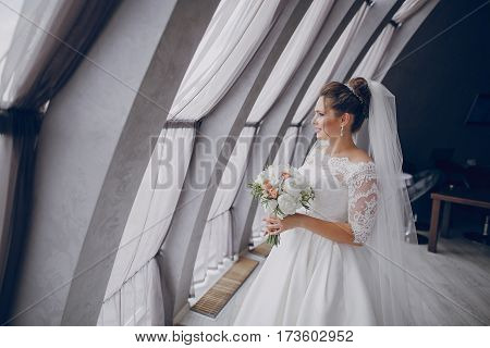 bride in a white dress and bouquet of flowers is at the high windows