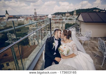 bride and groom sitting in a cafe on the summer terrace