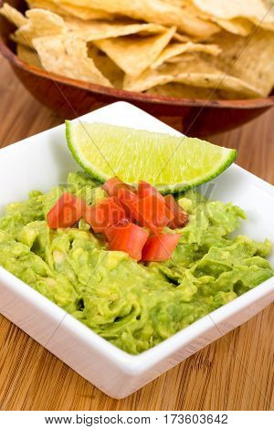 fresh guacamole dip with nacho close up