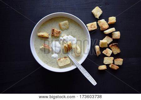 Broccoli cream soup with croutons on the black wooden table. vegetable soup.