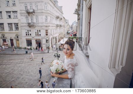 The bride standing on the balcony of a house in the background