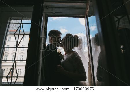 bride and groom standing by the window in the background and blue sky