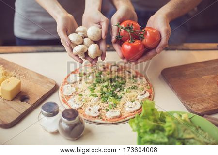 Pizza time. Close up photo of hands holding mushrooms and tomatoes. Young couple in kitchen. Family of two preparing food. Couple making delicious pizza