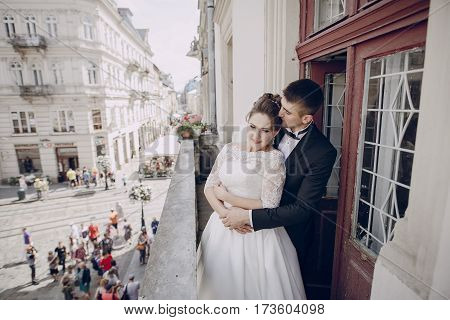 bride and groom standing on the balcony of a building in the background