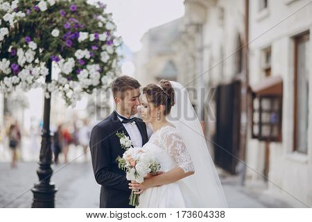 bride and groom walking along a sunny city with a bouquet of flowers