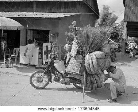 PHNOM PENH, CAMBODIA MARCH 24: A man will rides a motorcycle overloaded with straw baskets on March 24, 2012 in Phnom Penh, Cambodia.