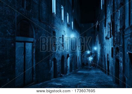 Street view with old buildings at night in Siena, Italy.