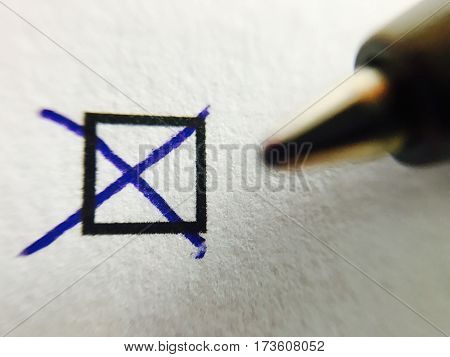 Check - Closeup of a ballpoint pen marking tick in check box, shallow depth of field with focus on checkmark