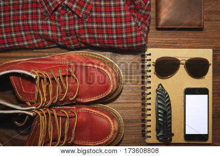 Worn but reliable boots chekered vintage shirt leather wallet recycled paper notebook cell phone knife and sunglasses