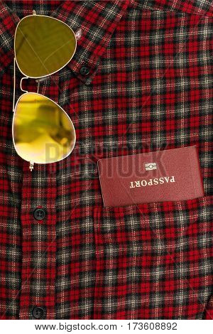 Male checkered cowboy's shirt with a passport in the pocket and sunglasses