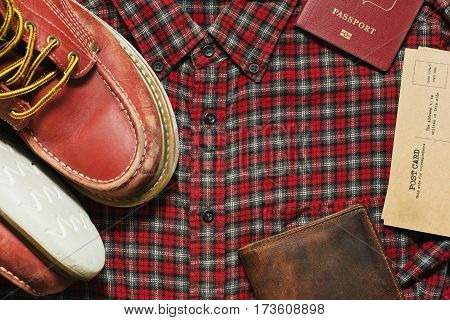 Old worn boots leather wallet vintage postcards and a passport on the checkered shirt