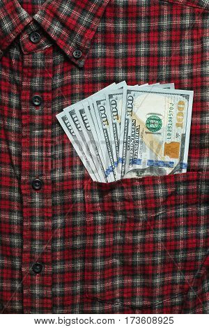 Male checkered cowboy's shirt with unsafely stored money in the pocket