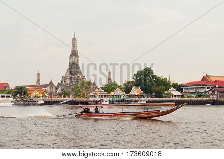 Cityscape with richly decorated biddhist temple and traditional thai longtail boat