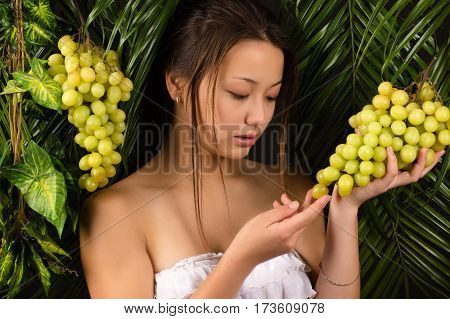 attractive teenager girl holding grapes in hands