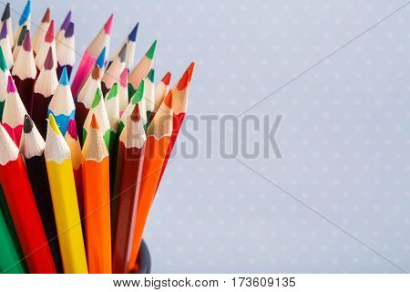 Color pencils in the container with light background. Colorful pencils in a variety of colors. Back to school concept. Toned picture. Background with point.