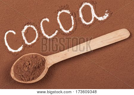 word cocoa written in cocoa powder with a wooden spoon.