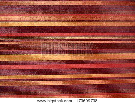 Texture of textile rug with striped pattern of red, yellow and brown colors