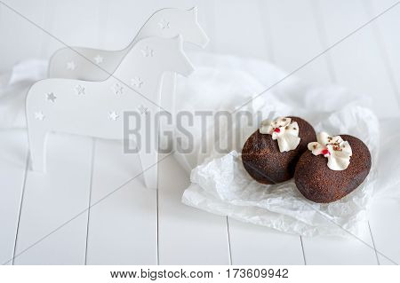 Cakes made of chocolate on transparent paper on a white background. Cakes decorated with red jelly and delicate white cream. White Horse.