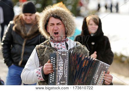 Orel Russia - February 26 2017: Maslenitsa fest. Man in fur hat playing bayan closeup