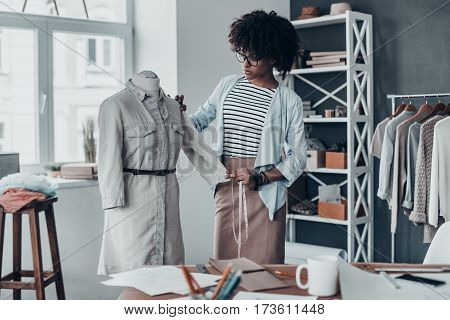 Young perfectionist. Beautiful young African woman measuring sleeve with tape while standing in her workshop with clothes hanging in the background