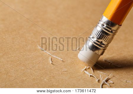 A pencil eraser removing a written mistake on a piece of paper. Brown paper. Orange pencil. White eraser. Writing. Painting. School and education.