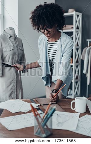 Her design is perfect. Beautiful young African woman measuring waist with tape and writing down the results while standing in her workshop