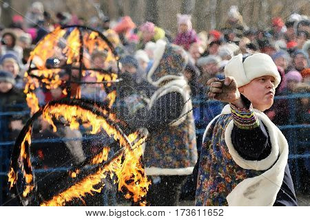 Orel Russia - February 26 2017: Maslenitsa fest. Fakir and crowd of people watching fire show closeup