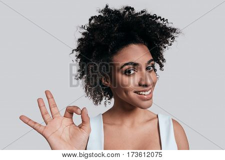 Everything is just fine. Young beautiful African woman in casual wear gesturing and looking at camera while standing against grey background