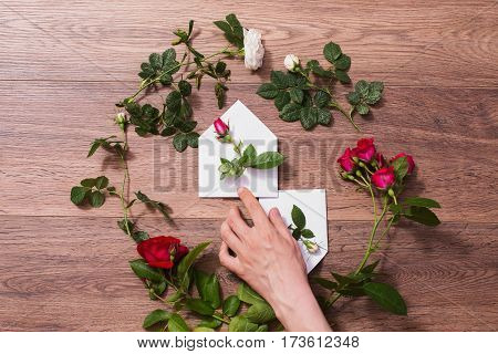 Hand holding white envelope with rose. Envelope and a white and red rose. Greeting card. Conceptual photography with rose. Wedding invitation card. Valentine day. Flat lay rose top view copyspace