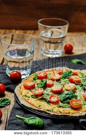 Cauliflower pizza crust with tomato and spinach.