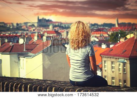 girl sitting on the roof of a house in Prague. top view of the city