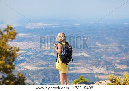 Female traveler with a backpack on her back enjoying the views from the mountains of Montserrat in Spain. The girl in a yellow dress on background of the nature