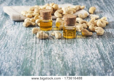 Cashew Nuts And Oil In Bottle On Wooden Background