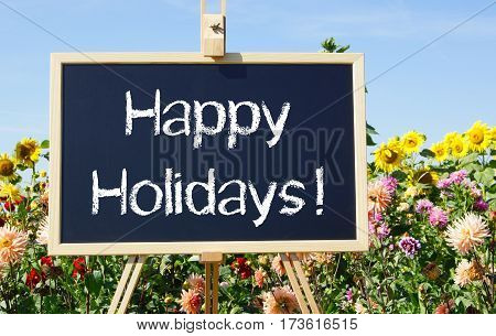 Happy Holidays - easel with text in the summer garden with flowers in the background